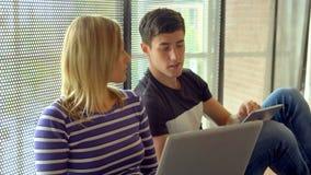 Estudiantes que trabajan junto en una asignación almacen de metraje de vídeo