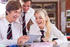 Estudiantes que usan el ordenador de la tablilla Imagenes de archivo