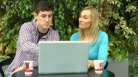 Estudiantes que usan el ordenador portátil afuera en campus almacen de metraje de vídeo