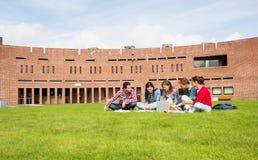 Estudiantes que usan el ordenador portátil en césped contra el edificio de la universidad Foto de archivo