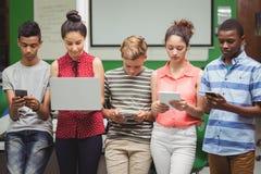 Estudiantes que usan el ordenador portátil, teléfono móvil, tableta digital Imágenes de archivo libres de regalías