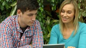 Estudiantes que usan la tableta afuera en campus metrajes
