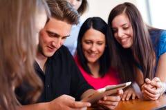Estudiantes que usan la tableta de Digitaces Foto de archivo libre de regalías