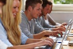 Estudiantes que usan las computadoras portátiles en clase Imagen de archivo libre de regalías