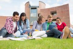 Estudiantes que usan las PC de la tableta en el césped contra el edificio de la universidad Fotos de archivo libres de regalías