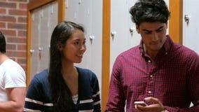 Estudiantes que usan smartphones en vestuario metrajes