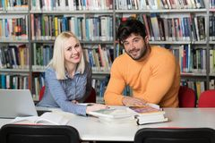 Estudiantes que usan una tableta en una biblioteca Imagenes de archivo