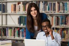 Estudiantes que usan una tableta en una biblioteca Foto de archivo libre de regalías