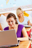Estudiantes: Schoolwork que hace adolescente en el ordenador portátil Fotografía de archivo libre de regalías