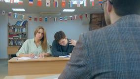Estudiantes serios que se sientan para las notas de una escritura del examen Foto de archivo libre de regalías