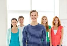 Estudiantes sonrientes con el adolescente en frente Imagenes de archivo
