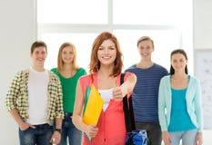 Estudiantes sonrientes con el adolescente en frente Imagen de archivo libre de regalías