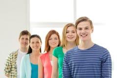 Estudiantes sonrientes con el adolescente en frente Imágenes de archivo libres de regalías
