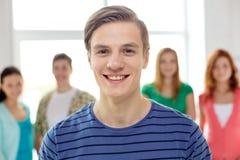 Estudiantes sonrientes con el adolescente en frente Fotografía de archivo