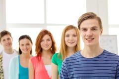Estudiantes sonrientes con el adolescente en frente Fotos de archivo libres de regalías