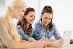 Estudiantes sonrientes con el ordenador de la PC de la tableta en la escuela Imagen de archivo libre de regalías