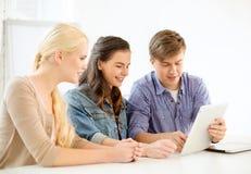 Estudiantes sonrientes con el ordenador de la PC de la tableta en la escuela Fotografía de archivo libre de regalías