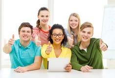 Estudiantes sonrientes con el ordenador de la PC de la tableta en la escuela Fotos de archivo