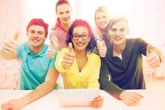 Estudiantes sonrientes con el ordenador de la PC de la tableta en la escuela Imagenes de archivo
