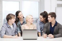 Estudiantes sonrientes con el ordenador portátil en la escuela Foto de archivo