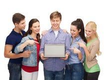 Estudiantes sonrientes con el ordenador portátil Fotografía de archivo libre de regalías