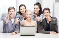 Estudiantes sonrientes con el ordenador portátil que muestra los pulgares para arriba Imagen de archivo libre de regalías