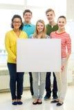 Estudiantes sonrientes con el tablero en blanco blanco en la escuela Imagen de archivo