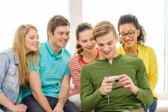 Estudiantes sonrientes con la cámara digital en la escuela Foto de archivo