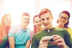 Estudiantes sonrientes con la cámara digital en la escuela Fotos de archivo libres de regalías