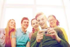 Estudiantes sonrientes con la cámara digital en la escuela Fotografía de archivo libre de regalías