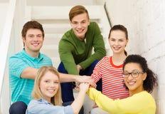 Estudiantes sonrientes con las manos encima de uno a Imágenes de archivo libres de regalías