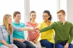 Estudiantes sonrientes con las manos encima de uno a Fotografía de archivo