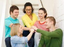 Estudiantes sonrientes con las manos encima de uno a Foto de archivo