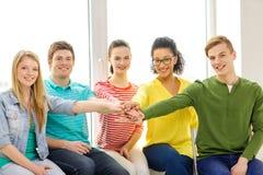 Estudiantes sonrientes con las manos encima de uno a Imagenes de archivo