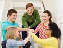 Estudiantes sonrientes con las manos encima de uno a Foto de archivo libre de regalías