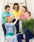 Estudiantes sonrientes con las manos encima de uno a Imagen de archivo libre de regalías