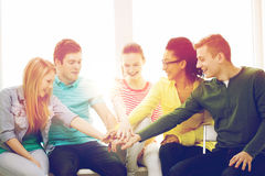 Estudiantes sonrientes con las manos encima de uno a Imagen de archivo