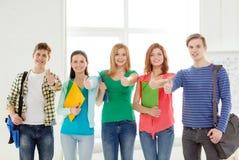 Estudiantes sonrientes con los bolsos y carpetas en la escuela Fotografía de archivo
