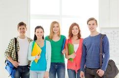 Estudiantes sonrientes con los bolsos y carpetas en la escuela Fotos de archivo