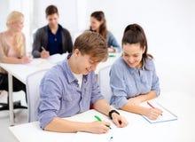 Estudiantes sonrientes con los cuadernos en la escuela Fotografía de archivo