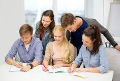Estudiantes sonrientes con los cuadernos en la escuela Imagen de archivo