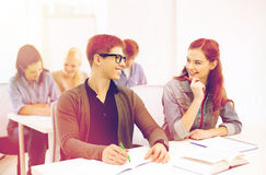 Estudiantes sonrientes con los cuadernos en la escuela Imagenes de archivo