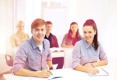 Estudiantes sonrientes con los cuadernos en la escuela Imagen de archivo libre de regalías