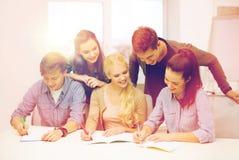 Estudiantes sonrientes con los cuadernos en la escuela Fotografía de archivo libre de regalías