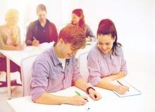 Estudiantes sonrientes con los cuadernos en la escuela Foto de archivo