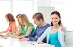 Estudiantes sonrientes con los libros de texto en la escuela Imagen de archivo