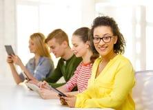 Estudiantes sonrientes con PC de la tableta en la escuela Imágenes de archivo libres de regalías
