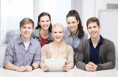 Estudiantes sonrientes con PC de la tableta en la escuela Imagen de archivo libre de regalías