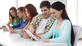 Estudiantes sonrientes con PC de la tableta en la escuela almacen de metraje de vídeo
