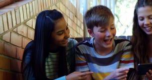 Estudiantes sonrientes de la escuela que se sientan en la escalera usando el teléfono móvil metrajes